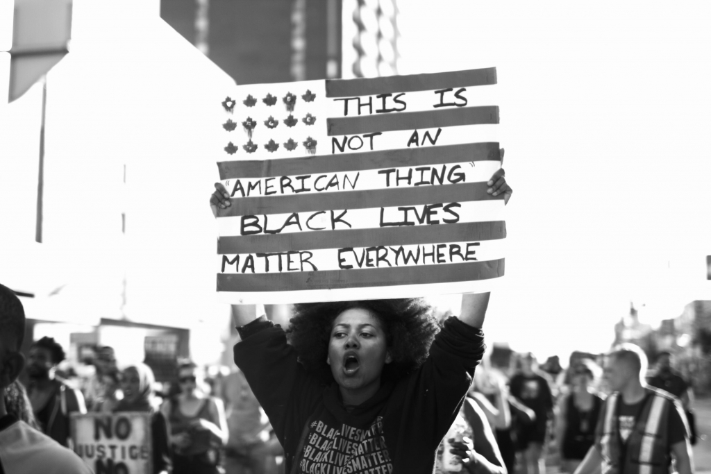 Jalani Morgan: Untitled, Toronto (2015). Anti-Blackness is global, as is our resistance. A marcher at a 2015 protest raises a sign to reinforce that state violence and oppression isn''t exclusive to America.